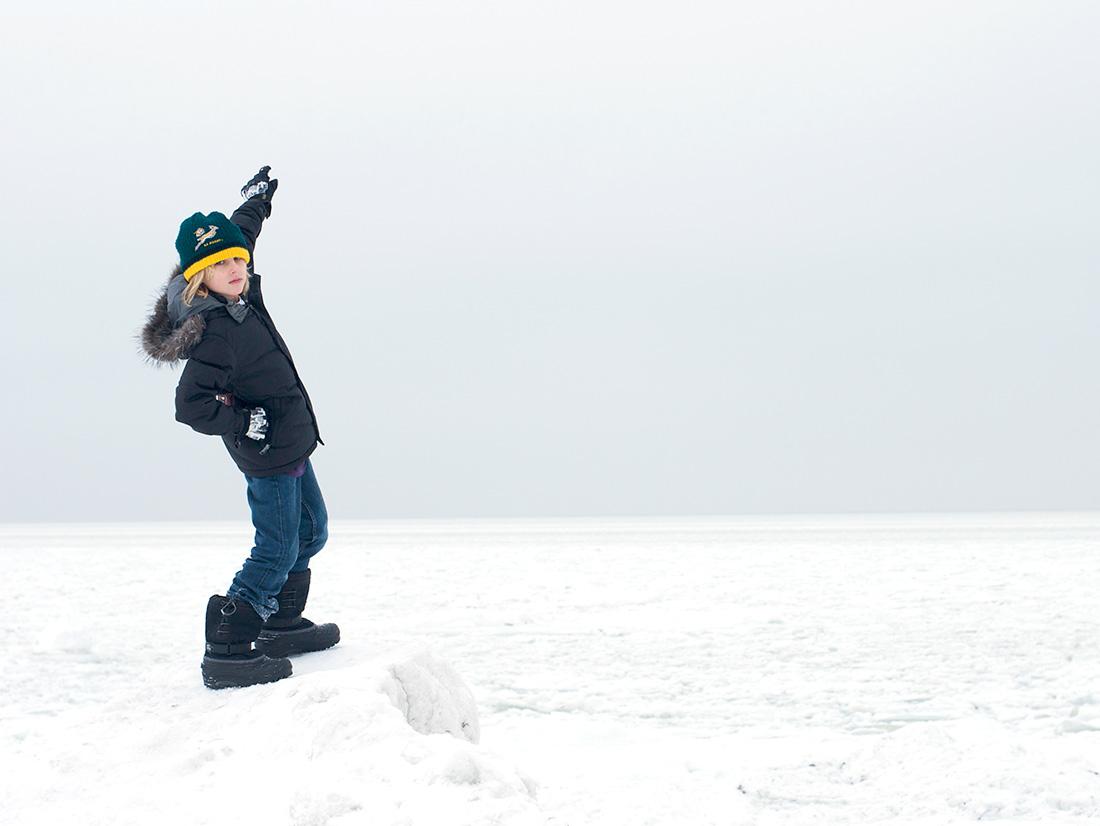 Junge im Winter an der zugefrorenen Ostsee